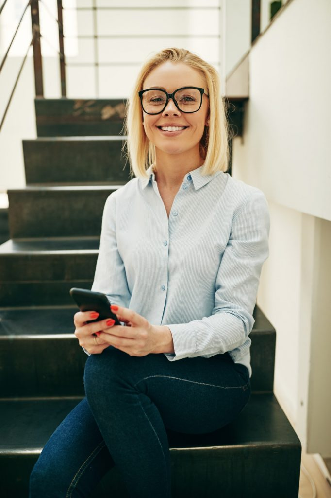Smiling businesswoman sitting on stairs sending texts on her phone