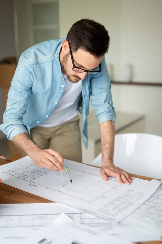 Portrait of adult architect working on plans and blueprints
